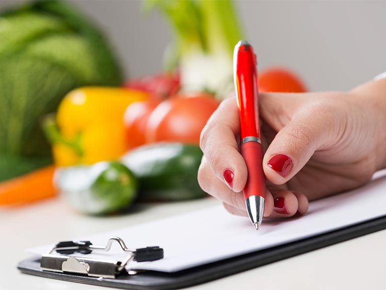 Dietician writing on clipboard